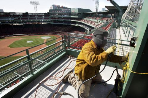 Wade Sutton of Merrimack, N.H., welds a column on the new section of upper deck seats in left field. ALSO: Hawk attacks girl at Fenway