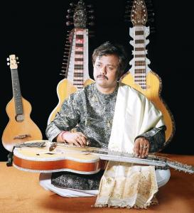 In addition to the slide guitar, Debashish Bhattacharya plays the 14-string gandharvi and the anandi, a four-string slide ukulele.