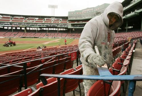 Painter Elber Macario, of Lynn, touched up a railing in the stands.