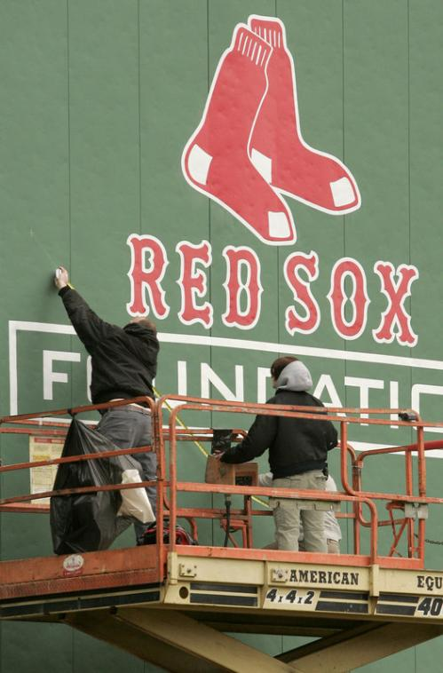 Workers put the finishing touches on a sign on the Green Monster.