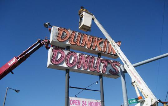 A crew dismantles the vintage Dunkin' Donuts neon sign at Market and North Beacon, making way for a modern version.
