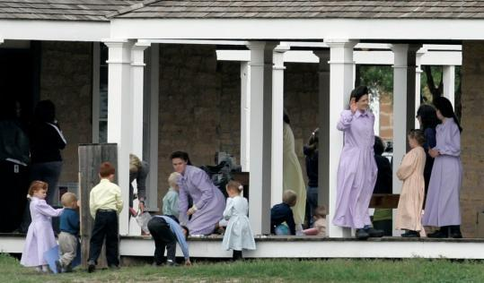 Women and children gathered on a porch at their temporary housing in San Angelo, Texas. Officials say they had the legal grounds to take action after a girl called a family violence shelter.