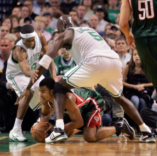 Rajon Rondo (left) and Kevin Garnett have the Bucks' Ramon Sessions surrounded - and floored - during first-quarter action.