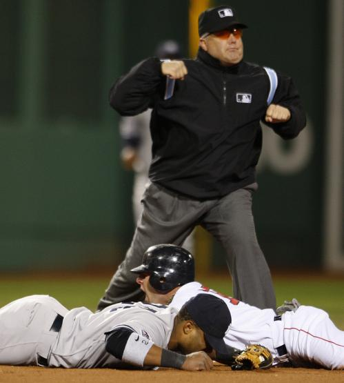 Umpire Brien O'Nora calls out Dustin Pedoria after the Red Sox second baseman tried to stretch a single into a double in the sixth inning and was tagged out by Robinson Cano.