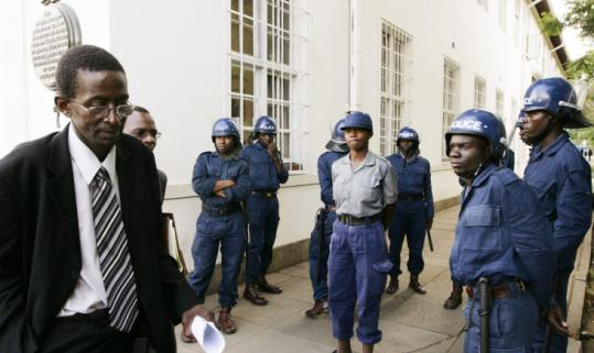 Zimbabwe's election commission lawyer George Chikumbirike left the high court under heavy police guard after the ruling.