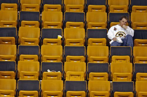 A disappointed Bruins fan sits alone in the stands after a Game 4 loss for the home team.