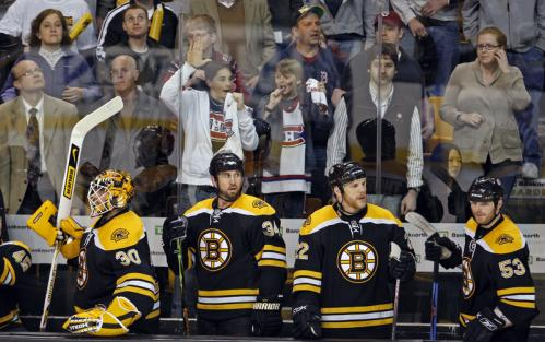 The Bruins bench (left to right) Tim Thomas, Shane Hnidy, Shawn Thornton, and Jeremy Reich, along with most of ther fans, wear a disappointed look as the clock runs out in the game, but two young Canadiens fans behind the bench are enjoying themselves.