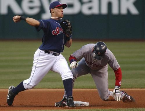 Cleveland's Asdrubal Cabrera (left) forces out Red Sox second baseman Dustin Pedroia while turning a double play in the first inning.