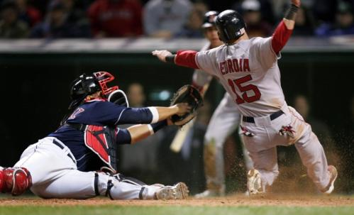 Dustin Pedroia (15) eludes the tag of Cleveland Indians catcher Victor Martinez in the ninth inning of a baseball game, but also missed the plate and was eventually tagged out by Martinez.