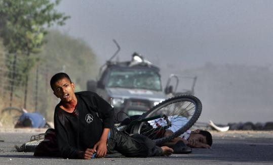 Palestinian youths lay on the ground after a missile struck the vehicle of Reuters cameraman Fadel Shana. Shana, who was filming Israeli tank movements, was killed in the strike, one of four missiles fired yesterday from an Israeli helicopter