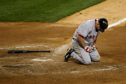 Kevin Youkilis crouches on the ground after fouling a pitch off his foot.