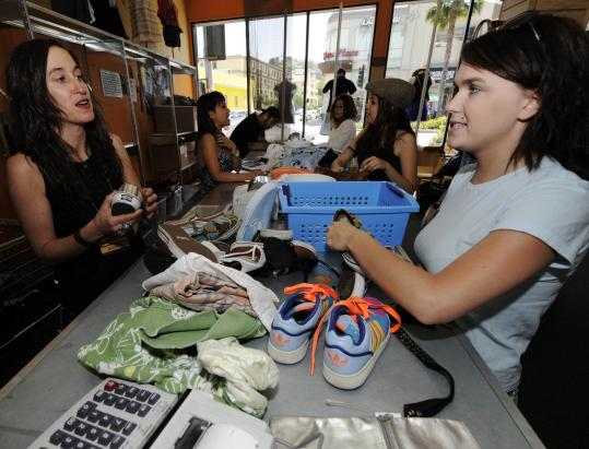 Alyssa Kamatainen (right) sells her shoes and shorts to store manager Monika DeClay at Buffalo Exchange in Los Angeles. Secondhand clothing chains have seen business surge this year.