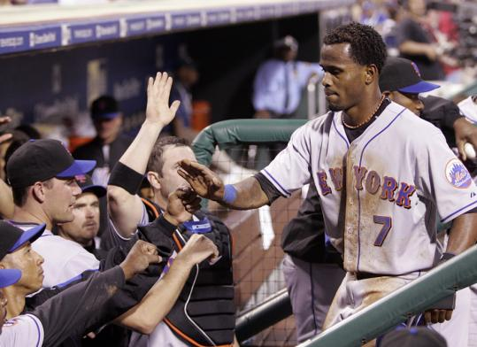 The Mets' Jose Reyes gets a friendly hand from his teammates after scoring on David Wright's triple in the third inning of New York's victory.