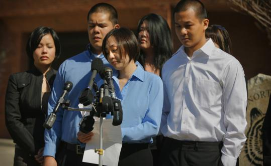 Nancy Chang (at microphone), sister of Lauren Chang, addressed the media outside of Newton North High School yesterday with her other siblings, Marcus (second from left) and Jason.