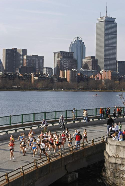 The first group of runners pass the 4.5 mile mark near the Longfellow Bridge with the Back Bay of Boston and the Charles River in the background.