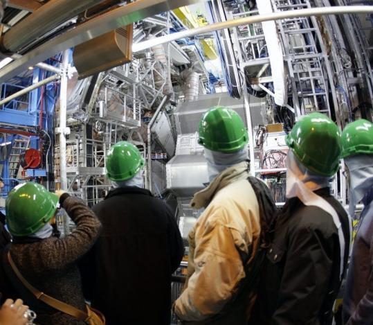 Visitors stand in front of the ATLAS detector at the Large Hadron Collider near Geneva.