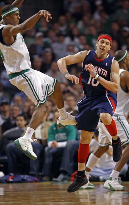 Rajon Rondo, left, goes airborne as he dishes the ball off despite the defense of Mike Bibby.