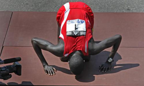 Men's winner Robert Kipkoech Cheruiyot from Kenya kisses the ground after winning his fourth consecutive Boston Marathon.