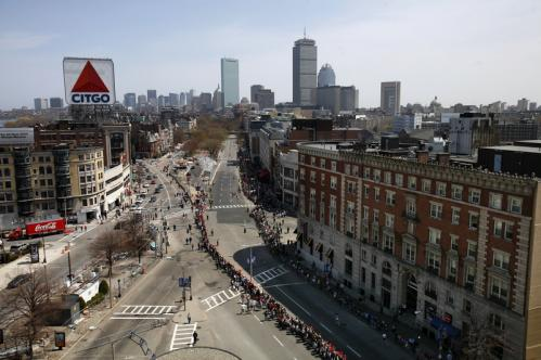 Runners stream through Kenmore Square as they neared the finish line of the Boston Marathon.