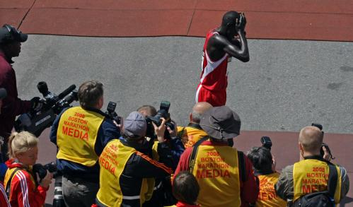 Men's champion Robert Kipkoech Cheruiyot from Kenya passes a group of photographers after crossing the finish line.