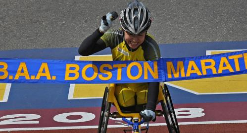 Women's wheelchair winner Wakako Tsuchida breaks the tape at the finish line.