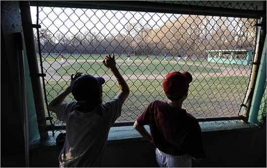 Will Kramer (left) and a teammate watch a Little League practice game.