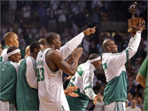Kevin Garnett raises the NBA's Defensive Player of the Year trophy surrounded by his teammates.
