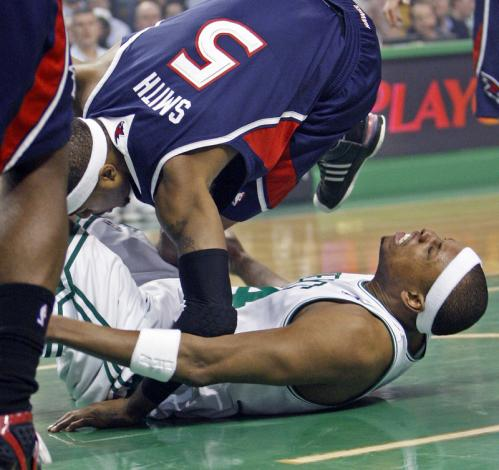Celtics captain Paul Pierce is in pain after getting tangled up with the Hawks' Josh Smith under the basket in the first quarter.