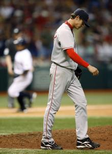 As Akinori Iwamura (background) heads for home, Clay Buchholz keeps his head down after allowing a two-run homer to the Tampa Bay second baseman in the eighth inning.