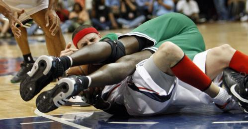 Atlanta's Mike Bibby finds himself underneath Kevin Garnett as they battle for a second-half loose ball.