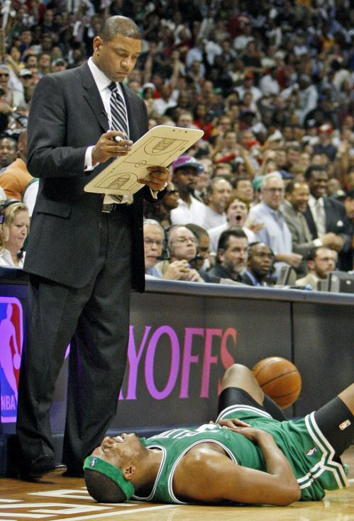 Celtics captain Paul Pierce writhes in pain in front of coach Doc Rivers.