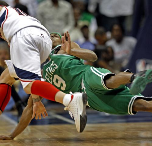 Boston's Rajon Rondo (9) tries to draw an offensive foul on Atlanta's Mike Bibby as he drives to the basket.