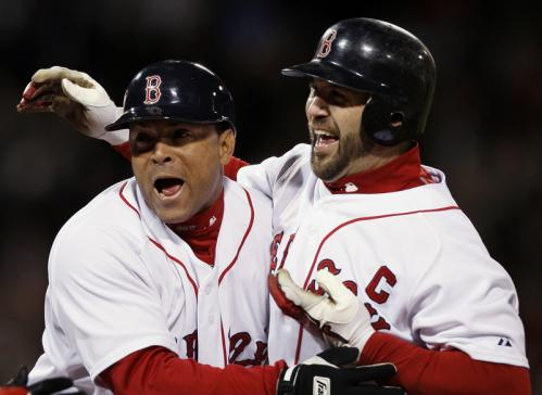 Boston's Jason Varitek, right, is hugged by coach Luis Alicea after Varitek's game-winning RBI single during the ninth inning.