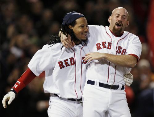 Boston's Manny Ramirez, left, is hugged by teammate Kevin Youkilis after Ramirez scored the winning run on Jason Varitek's RBI single during the ninth inning.