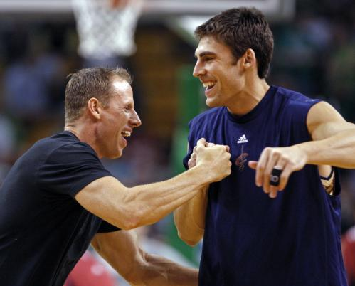 Former Celtics and current member of the Cavs Wally Szczerbiak is greeted by Boston's strength and conditioning coach Walter Norton during pregame warmups.