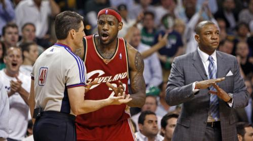 Cleveland's LeBron James argues with an official after he was called for a fourth-quarter traveling violation in front of the Boston bench, while Celtics head coach Doc Rivers calmly calls a timeout.