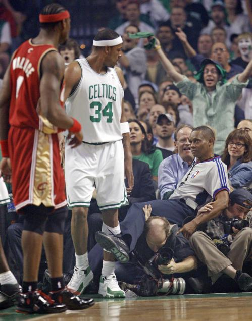 Boston's Paul Pierce watches as a referee tumbles into a row of photographers.