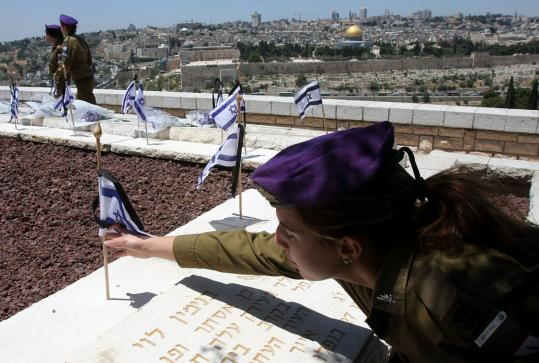 A soldier placed flags yesterday on the graves of Jews killed during Israel's 1948 War of Independence. The flags at the Mount of Olives cemetery are part of Israel's 60th anniversary.