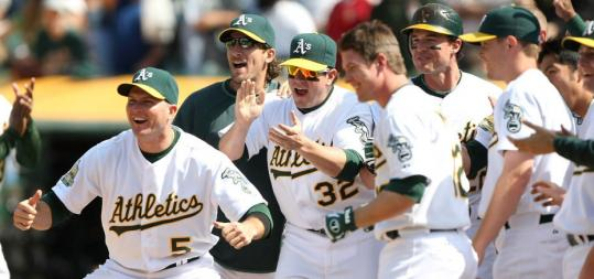 Oakland's Mike Sweeney (left) and his teammates wait to greet Mark Ellis at the plate after Ellis's walkoff home run against the Orioles in the 10th inning.