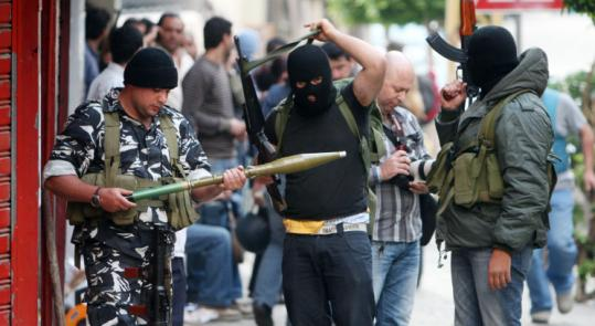 Shi'ite opposition militiamen checked weapons yesterday during clashes with pro-government supporters in