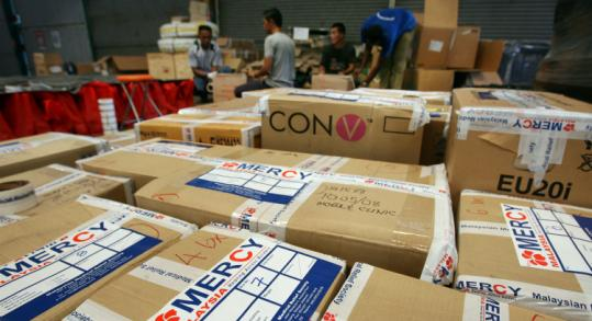 Malaysian aid workers packed food and medical supplies bound for Burma at a warehouse in Kuala Lumpur yesterday.