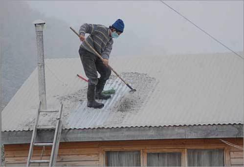 A man sweeps the volcanic ash from the roof of his house in Futaleufu.