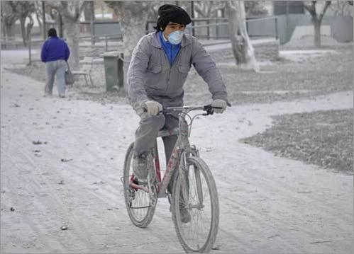A man rides his bike along a street covered with ashes with his mouth covered with a mask in Esquel, some 994 miles southwest of Buenos Aires on May 6.