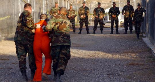 Police escorted a detainee to his cell at Guantanamo Bay in Cuba in this file photograph taken Jan. 11, 2002. Republican John McCain and Democrats Hillary Clinton and Barack Obama have said the facility should be closed.