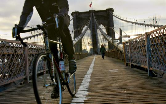 A morning commuter traverses the Brooklyn Bridge. Many find that bicycling has economical and ecological advantages.