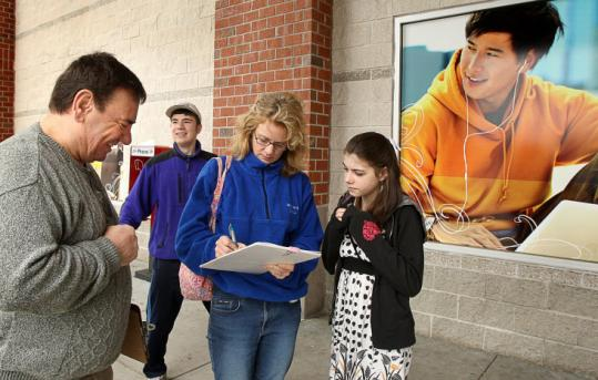 Alvin Anders approached shoppers in Framingham to get signatures for the initiative to eliminate the state income tax.