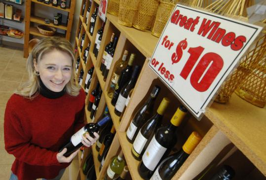 Wine Rack owner Jocelyn Vorbach shows a bottle of wine for $10 - a price that's now more attractive even to the well-off.
