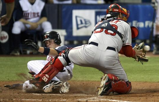 Despite catcher Jason Varitek's best efforts, Michael Cuddyer slides safely into home in the Twins' three-run fifth inning.