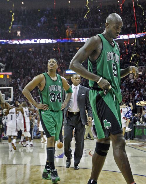 Paul Pierce (34), head coach Doc Rivers and Kevin Garnett (5) leave the court after a Game 4 loss, while the Cavaliers celebrate behind them.