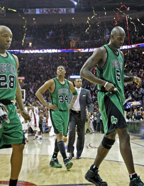 Sam Cassell (28), Paul Pierce (34), head coach Doc Rivers and Kevin Garnett (5) walk off the floor as the Cavaliers celebrate in the background.
